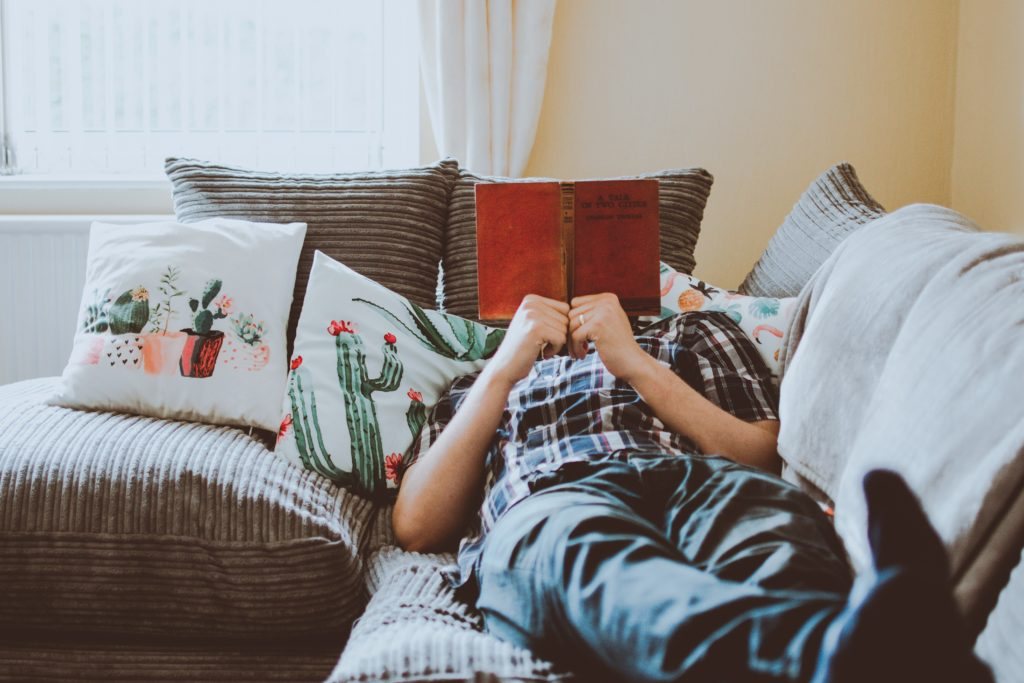 person-laying-on-sofa-while-reading-book-1471991